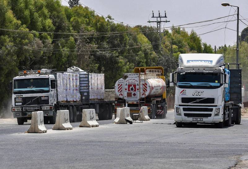 Drivers sit at their trucks at the Kerem Shalom crossing, the main passage point for goods entering Gaza from Israel, in the southern Gaza Strip town of Rafah, following a partial reopening of the crossing point on July 24, 2018. Israel partially reopened its only goods crossing with the Gaza Strip today after a two-week closure prompted by border tensions and incendiary kites sparked fears of a severe fuel shortage in the blockaded Palestinian enclave. Fuel trucks began entering through the Kerem Shalom crossing at noon, while food and medicine deliveries that had not been subject to the closure were set to continue. / AFP / SAID KHATIB