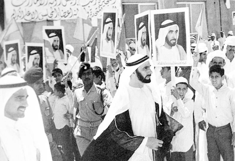 Picture shows President of the United Arab Emirates Sheikh Zayed bin Sultan al-Nahyan walking past supporters receiving him in the emirate of Fujairah  during his visit 03 January 1972. (Photo by WAM / AFP)