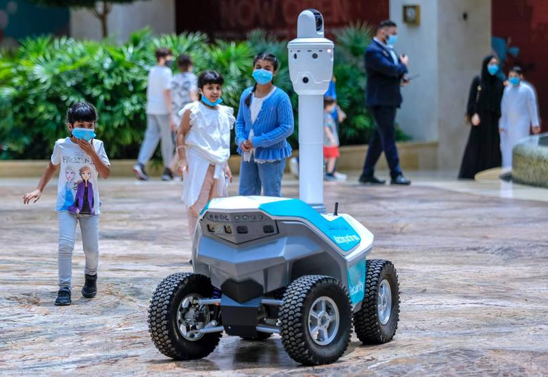Abu Dhabi, United Arab Emirates, August 19, 2020.     Children are amazed at a roving robot on wheels which does thermal checks around the Yas Mall.Victor Besa /The NationalSection:  NAReporter:  Haneen Dajani