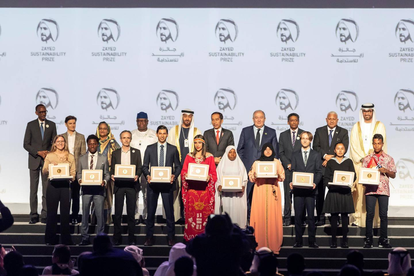 ABU DHABI, UNITED ARAB EMIRATES. 13 JANUARY 2020. The Zayed Sustainability Awards held at ADNEC as part of Abu Dhabi Sustainability Week. The winners from Top row center is H.E. Sheikh Mohammed bin Zayed Al Nahyan, Crown Prince of Abu Dhabi and Deputy Supreme Commander of the United Arab Emirates Armed Forces. LtoR in the bottom row: Health Winner: Globhe, Sweden. Food Winner: Okuafu Foundation, Ghana. Energy Winner: Electricians Without Borders, France. Water Winner: Ceres Imaging, USA. Global High Schools Winner: The Americas, Air Batalla, Columbia. Global High Schools Winner: Sub Sahara Africa, HakimiAliyu Day Secondary School, Nigeria. Global High Schools Winner: Middle East and North Africa, Al Amal Junior High School, Morocco. Global High Schools Winner: Europe and Central Asia, United World College Mostar, Bosnia and Herzegovina. Global High Schools Winner: South Asia, Bloom Nepal School, Nepal. Global High Schools Winner: East Asia and Pacific, Eutan Tarawa IETA Junior Secondary School, Kiribati. (Photo: Antonie Robertson/The National) Journalist: Kelly Clarker. Section: National.