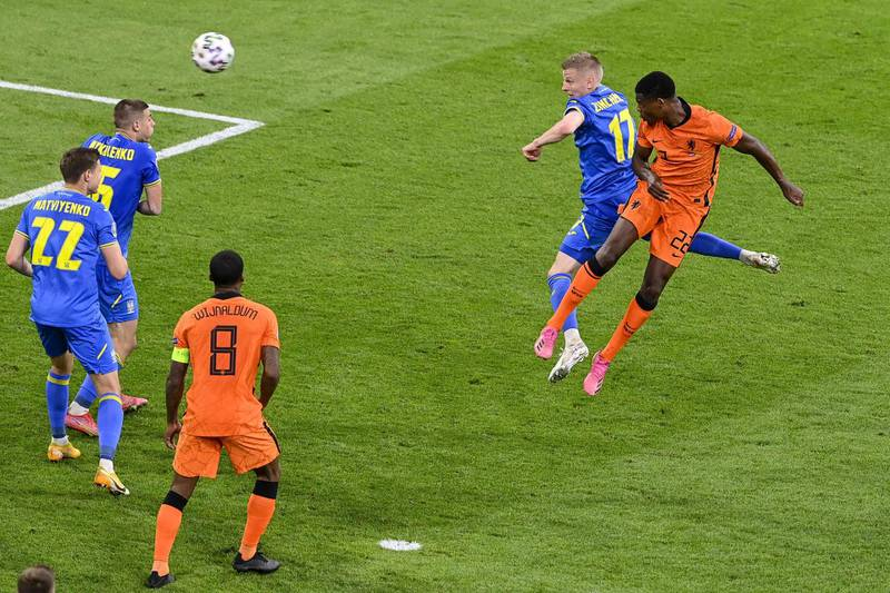 TOPSHOT - Netherlands' defender Denzel Dumfries (R) heads the ball to score the third goal during the UEFA EURO 2020 Group C football match between the Netherlands and Ukraine at the Johan Cruyff Arena in Amsterdam on June 13, 2021. / AFP / POOL / Olaf Kraak