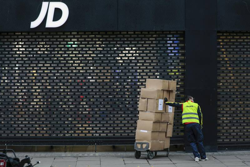 A delivery courier waits with a trolley of boxes outside a closed JD Sports Fashion Plc store on Oxford Street in central London, U.K., on Monday, Nov. 30, 2020. Philip Green'sArcadiaGroup is poised to seek protection from creditors and become the most notable U.K. retail insolvency since the beginning of the coronavirus pandemic. Photographer: Jason Alden/Bloomberg