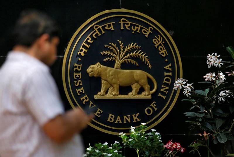 FILE PHOTO: A man checks his phone outside the Reserve Bank of India (RBI) headquarters in Mumbai, India, April 5, 2018. REUTERS/Francis Mascarenhas/File Photo