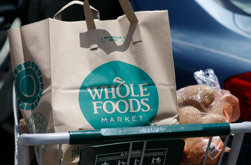FILE - In this Friday, June 16, 2017, file photo, groceries from Whole Foods Market sit in a cart before being loaded into a car, outside a store in Jackson, Miss. On Wednesday, Aug. 23, 2017, Whole Foods shareholders will be voting on whether to approve Amazon's $13.7 billion takeover bid of the organic grocer. (AP Photo/Rogelio V. Solis, File)