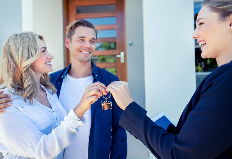 Real estate agent giving a young couple the key to their new house. The house is contemporary. All are happy and smiling. The couple are casually dressed and the agent is in a suit. The front door is also visible. Copy space