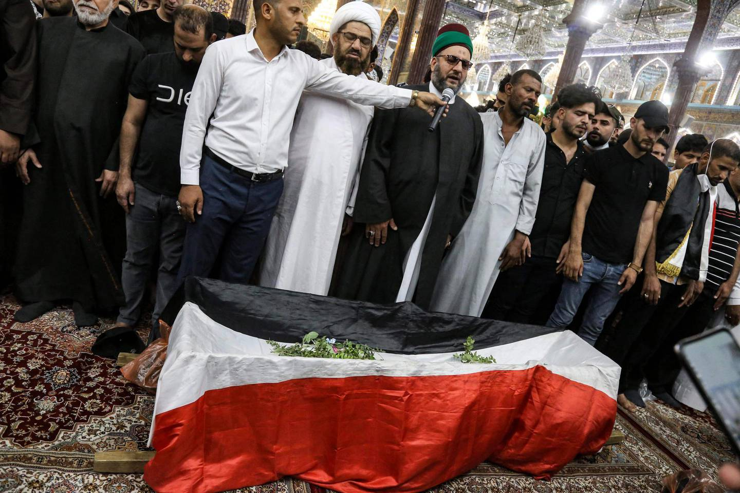 Mourners pray by the body of Iraqi anti-government activist Ihab al-Wazni (Ehab al-Ouazni) during his funeral at the Imam Hussein Shrine in the central holy shrine city of Karbala on May 9, 2021. Wazni, a coordinator of protests in the Shiite shrine city of Karbala, was a vocal opponent of corruption, the stranglehold of Tehran-linked armed groups and Iran's influence in Iraq. He was shot overnight outside his home by men on motorbikes, in an ambush caught on surveillance cameras. He had narrowly escaped death in December 2019, when men on motorbikes used silenced weapons to kill fellow activist Fahem al-Tai as he was dropping him home in Karbala, where pro-Tehran armed groups are legion. / AFP / Mohammed SAWAF