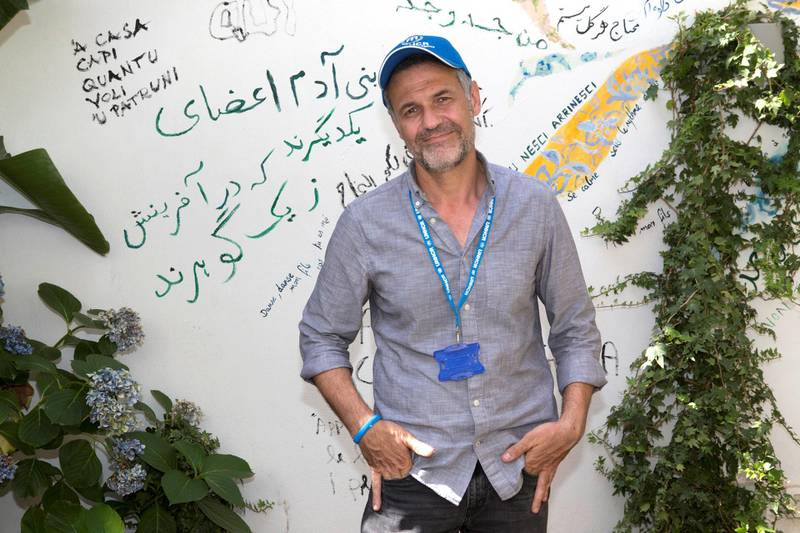 Khaled Hosseini writes a poem on the walls of of the Orient experience restaurant. ; UNHCR Goodwill Ambassador Khaled Hosseini meets refugees on the Italian island of Sicily. UNHCR/Andy Hall