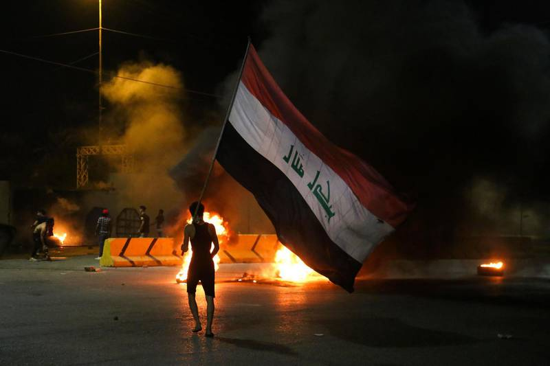 (FILES) In this file photo taken on May 9, 2021 Iraqi protesters burn tyres in front of the Karbala governorate headquarters in the central  city of Karbala following the assassination of a local anti-government activist. A wave of attacks on pro-democracy activists and journalists in Iraq have sparked mounting calls to boycott October parliamentary elections, as perpetrators go unpunished. More than 70 activists have died in targeted killings and dozens of others have been abducted or survived attacks since a protest movement demanding political overhaul and an end to endemic corruption shook Iraq from October 2019 to June 2020 / AFP / Mohammed SAWAF
