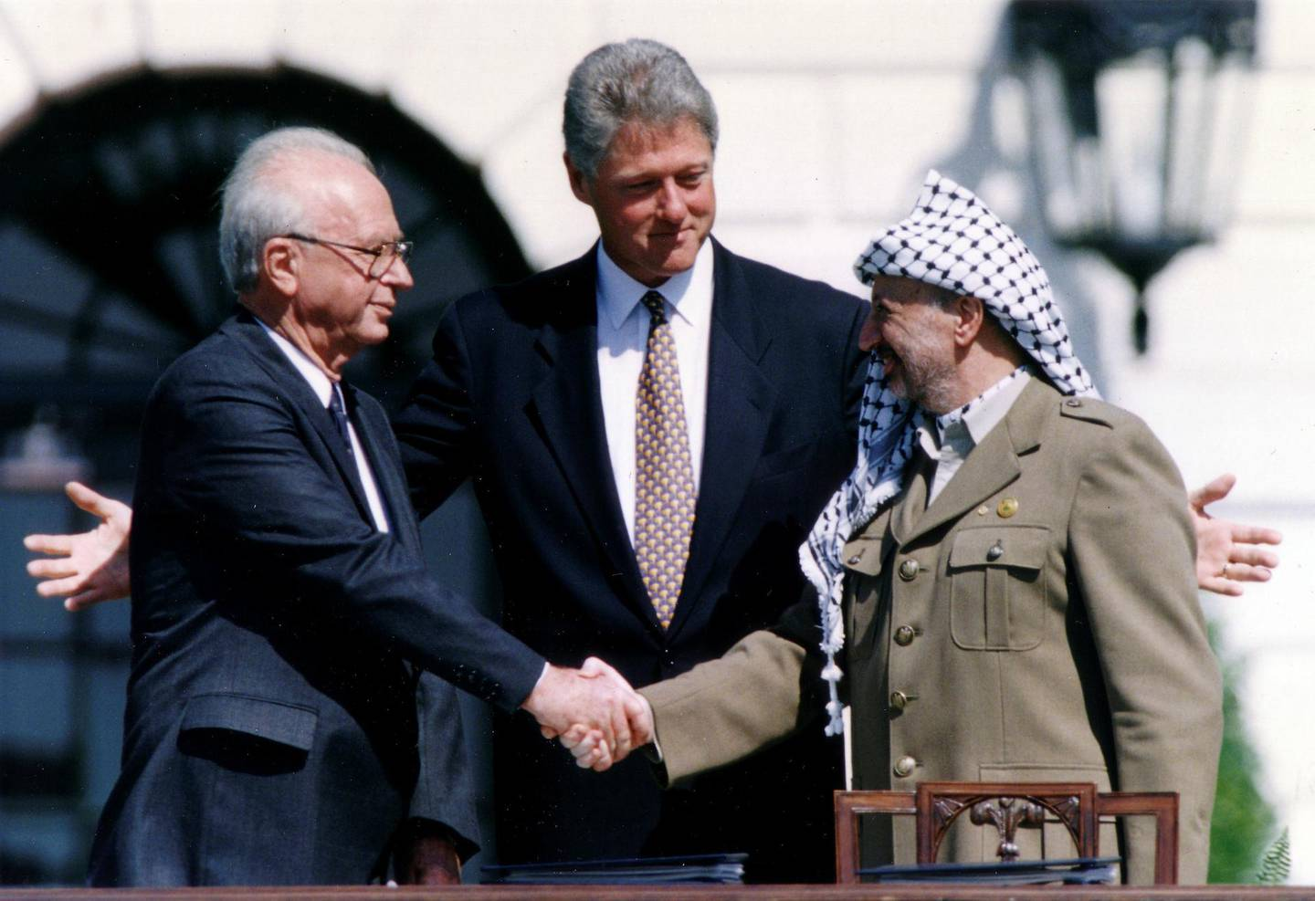 PLO Chairman Yasser Arafat (R) shake hands with Israeli Prime Minister Yitzhak Rabin (L), as U.S. President Bill Clinton stands between them, after the signing of the Israeli-PLO peace accord, at the White House in Washington September 13, 1993. REUTERS/Gary Hershorn (UNITED STATES - Tags: POLITICS)