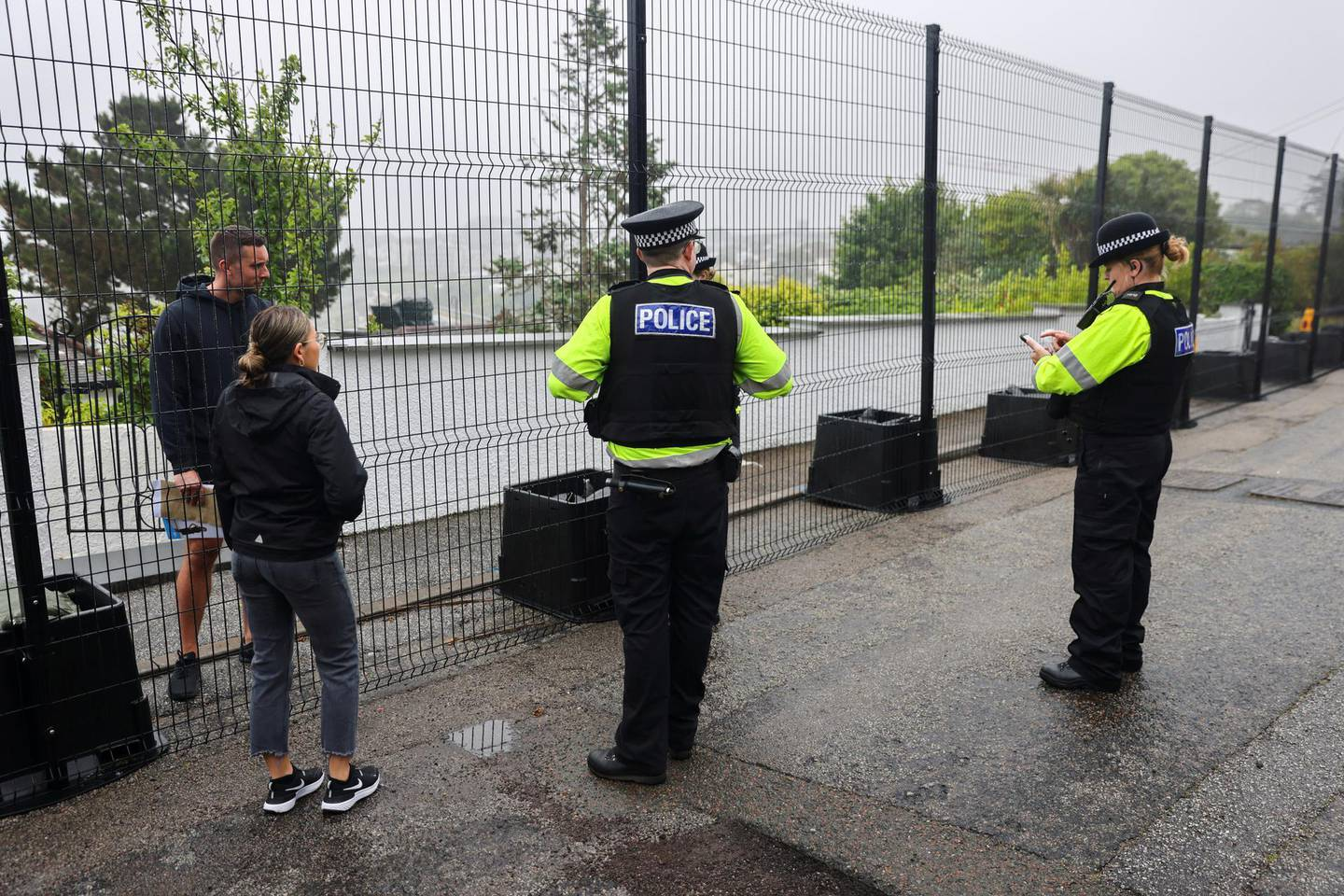 Police officers talk to residents by a newly erected fence in Carbis Bay, ahead of the G7 summit, in Cornwall, Britain, June 5, 2021. REUTERS/Tom Nicholson