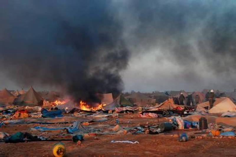 In this photo released by the MAP news agency (Maghreb Arabe Presse) shows Moroccan forces dismantle a camp housing thousands of refugees in the Western Sahara, near Laayoune, Monday Nov. 8, 2010. At least three Moroccan security officials were killed and 70 injured Monday in a raid on a protest camp in the disputed territory of Western Sahara and unrest that then spread to a nearby city, where several buildings were set on fire. (AP Photo/MAP/HO) *** Local Caption ***  CAS101_Morocco_Western_Sahara.jpg