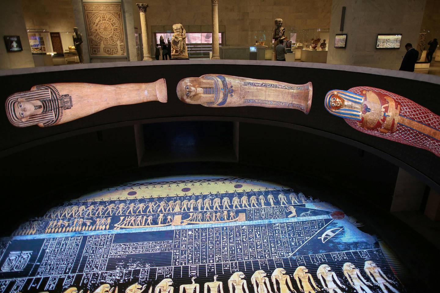 """People visit Egypt's new National Museum of Egyptian Civilisation (NMEC), in the Fustat district of Old Cairo, during its official reopening a day after the Pharaohs' Golden Parade ceremony, on April 4, 2021. - The NMEC which opened its doors to limited exhibits from 2017, opens fully a day after the """"Pharaohs' Golden Parade"""", but the mummies go on display to the general public two weeks later. (Photo by Mahmoud KHALED / AFP)"""