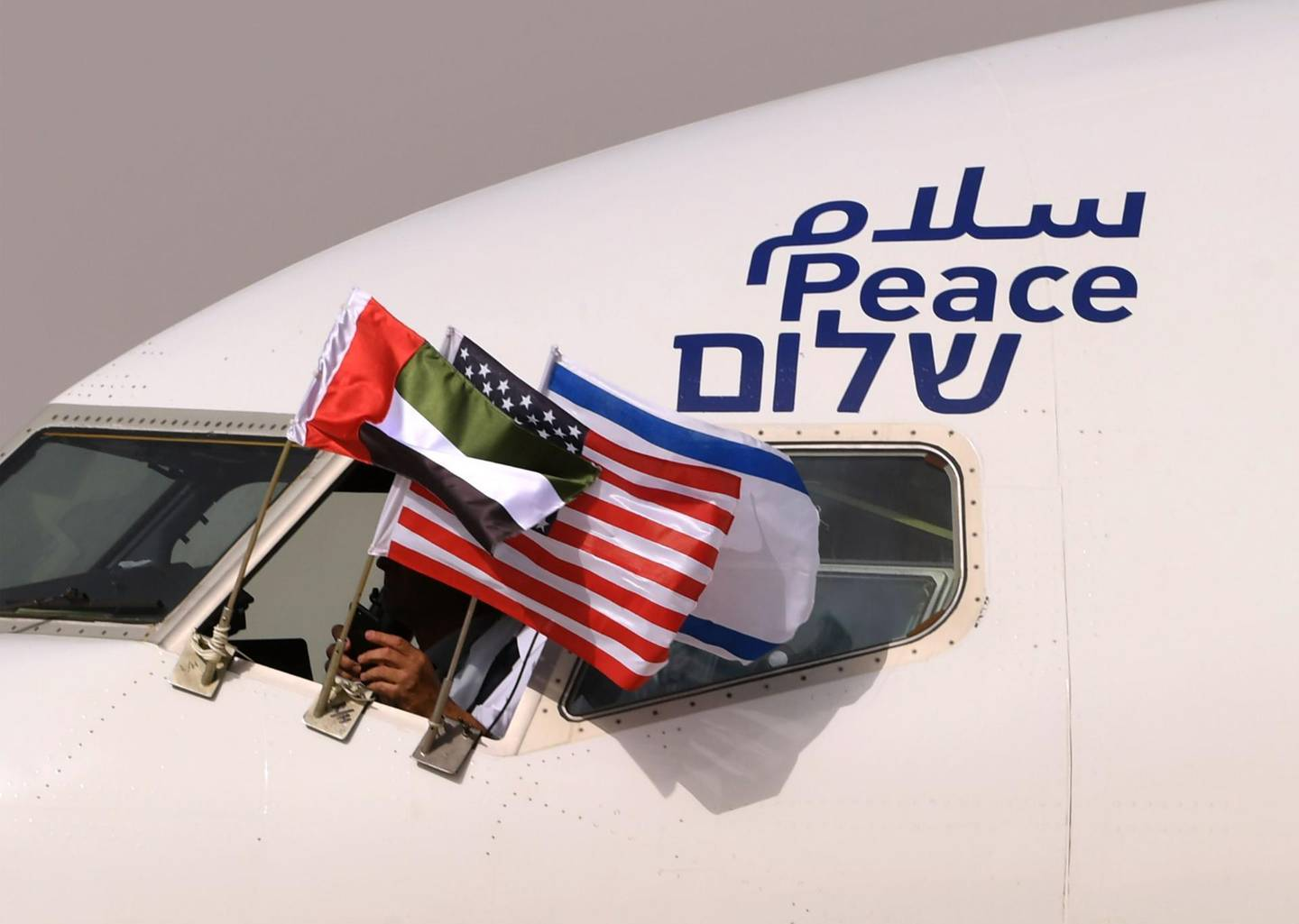 """(FILES) In this file photo taken on August 31, 2020, the Emirati, Israeli and US flags are picture attached to an air-plane of Israel's El Al, adorned with the word """"peace"""" in Arabic, English and Hebrew, upon it's arrival at the Abu Dhabi airport in the first-ever commercial flight from Israel to the UAE. Israel and the United Arab Emirates will sign a US-brokered agreement normalizing their relations at the White House on September 15, 2020 a US official said on September 8. / AFP / KARIM SAHIB"""