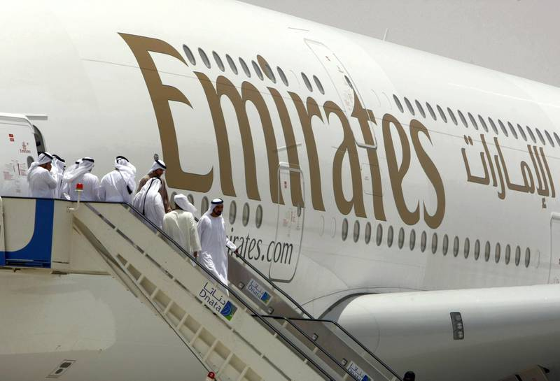 """Sheikh Mohammed bin Rashid al-Maktoum (front), prime minister of the United Arab Emirates and the ruler of Dubai, walks off an Emirates Airlines plane during the media tour of Dubai's new second airport, Dubai World Central or Al-Maktoum International, operational only to cargo until passenger facilities are completed, on July 1, 2010, in the desert on the outskirts of the Gulf emirate, where a 32 million dollar (26 million euro) new """"city"""" is being built to include a port.  AFP PHOTO/KARIM SAHIB (Photo by KARIM SAHIB / AFP)"""