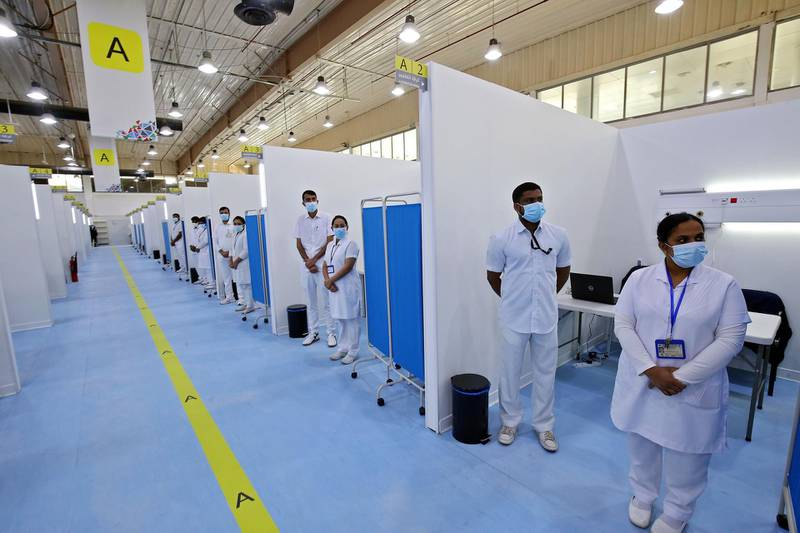 (FILES) In this file photo taken on December 23, 2020 Medical staff stand ready at the Kuwait vaccination center for COVID-19 at the International Fairgrounds in Kuwait City. Sports stadiums, cathedrals and theme parks the world over have been rapidly repurposed as temporary vaccination centres in a global drive to administer the life-saving jabs. / AFP / YASSER AL-ZAYYAT