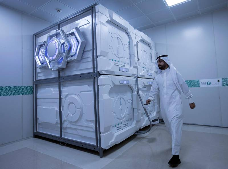 epa06955420 A hajj pilgrim exits his capsule room in Mecca, Saudi Arabia, 16 August 2018 (issued 18 August 2018). Hajj season pilgrims will be able to try out the latest mobile hotel capsules - sleeping units that offer hotel room services and facilities in the smallest possible space, Hadiyah, the Hajji and Mu'tamer's Gift Charitable Association has announced.  EPA/SEDAT SUNA