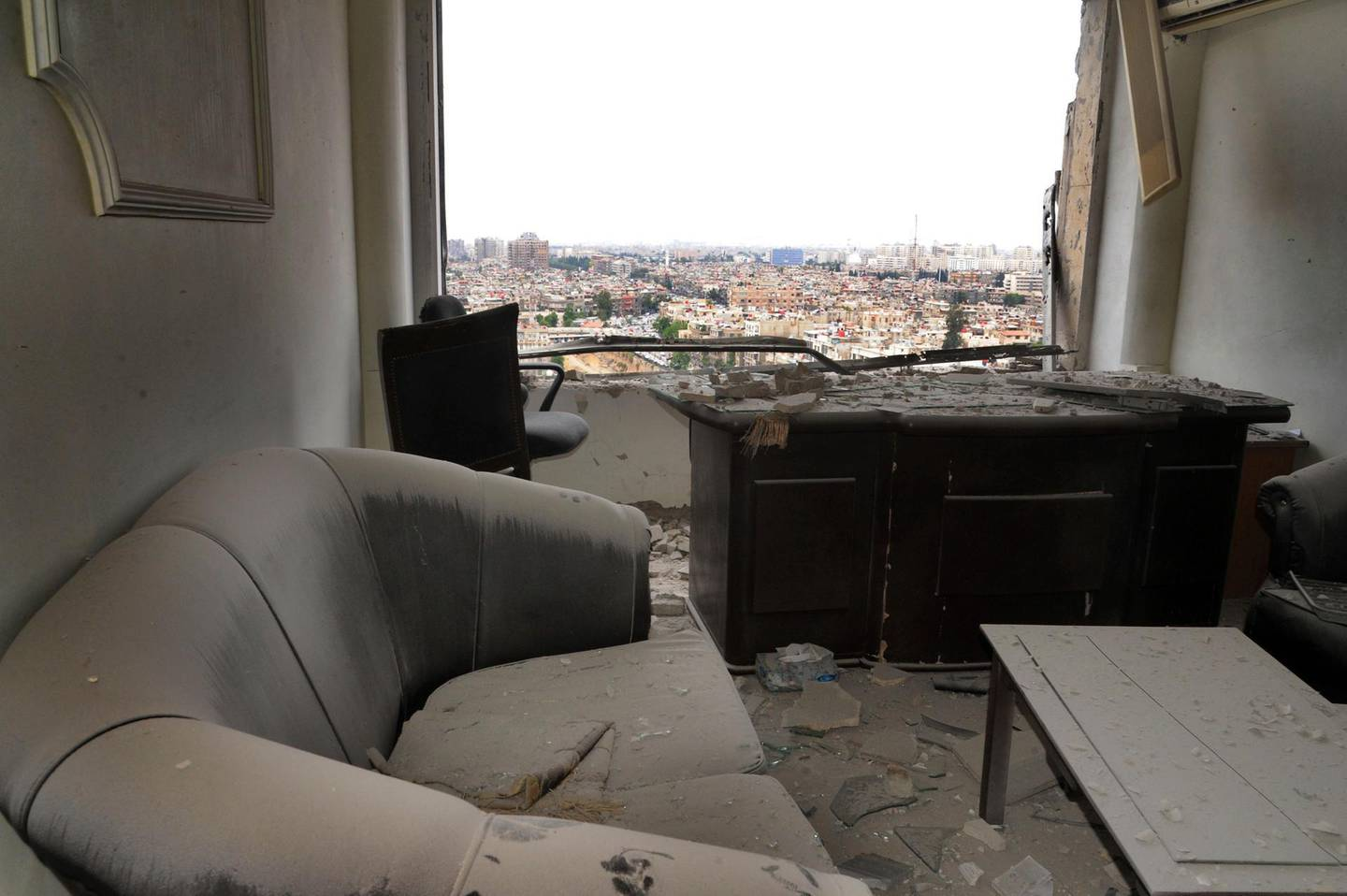This photo released by the Syrian official news agency SANA, shows damage inside a office that was hit by shelling, apparently by Islamic State fighters, in Damascus, Syria, Wednesday, May 9, 2018. Militants fired three mortar shells on the center of Damascus Wednesday killing several persons and wounding 14, Syria's state news agency said. (SANA via AP)