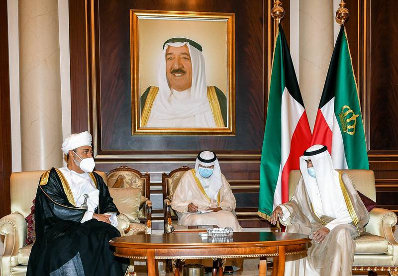 """A handout picture released by the press office of the Emir of Kuwait Diwan on October 1, 2020 shows Oman's Sultan Haitham bin Tariq al-Said (L) meeting with Kuwait's new Emir Sheikh Nawaf al-Ahmad al-Jaber Al-Sabah (R) and offering condolences to the latter, while mask-clad due to the COVID-19 coronavirus pandemic, at the Emiri Terminal of Kuwait International Airport. (Photo by - / EMIR OF KUWAIT DIWAN / AFP) / == RESTRICTED TO EDITORIAL USE - MANDATORY CREDIT """"AFP PHOTO / HO / EMIR OF KUWAIT DIWAN"""" - NO MARKETING NO ADVERTISING CAMPAIGNS - DISTRIBUTED AS A SERVICE TO CLIENTS =="""