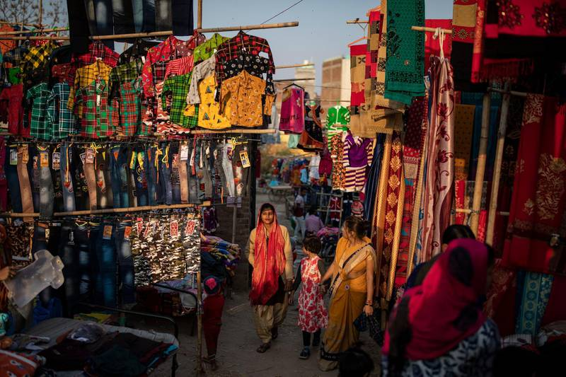 A woman walks through a market without a mask on the outskirts of New Delhi, India, Friday, Nov. 20, 2020. Authorities in capital New Delhi are fighting to head off nearly 7,500 new cases a day while ensuring that the flagging economy doesn't capsize again. The government hiked the fine for not wearing a mask four times to 2,000 rupees ($27) as it considered fresh restrictions. (AP Photo/Altaf Qadri)
