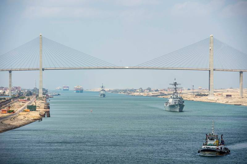The guided-missile cruiser USS Monterey (CG 61), left, and the guided-missile destroyer USS Thomas Hudner (DDG 116) sail behind the aircraft carrier USS Dwight D. Eisenhower (CVN 69) during a Suez Canal transit, in this picture taken April 2, 2021 and released by U.S. Navy on April 3, 2021. Sophie A. Pinkham/U.S. Navy/Handout via REUTERS ATTENTION EDITORS- THIS IMAGE HAS BEEN SUPPLIED BY A THIRD PARTY.