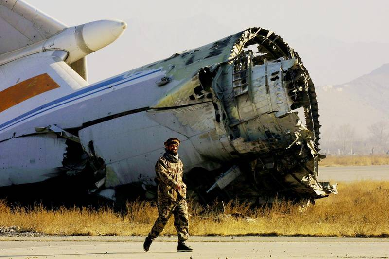399310 16: An Afghan Northern Alliance soldier walks by the wreckage of an aircraft at Kabul International Airport January 7, 2002 as the airport prepares to reopen to international flights shortly. (Photo by Paula Bronstein/Getty Images)
