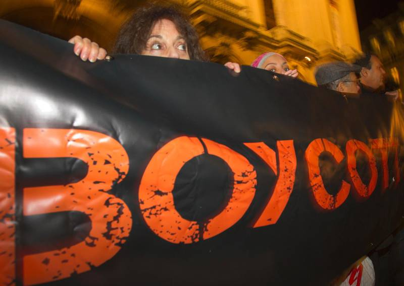 """FILE - In this Wednesday, Oct. 31, 2012 file photo, French demonstrators and supporters of Palestinians of the BDS movement hold a placard with the word """"Boycott"""" during a demonstration in Paris. The European Court of Human Rights ruled Thursday June 11, 2020 that France violated the freedom of expression of pro-Palestinian activists who were convicted for campaigning against Israeli goods. (AP Photo/Jacques Brinon, File)"""
