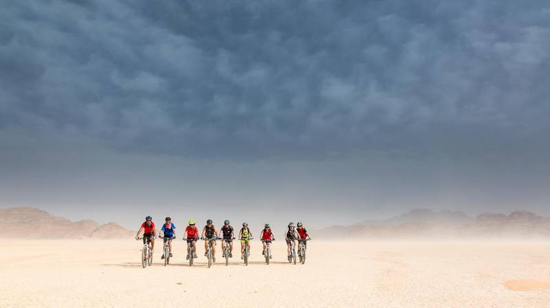 A Group of experienced Mountainbikers is enjoing the ride in the Jordan desert on a driet out lake. Due to the heavy winds during a thunderstorm the air is full of sand but the sunlight is gaining more and more the mastery.