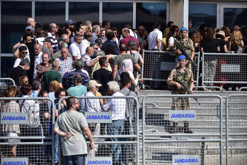 Turkish soldiers stand outside the court in a prison complex where the trial of prominent philanthropist Osman Kavala and 15 others started, while people arrive, in Silivri, outside Istanbul, Monday, June 24, 2019. The defendants went on trial in Turkey Monday accused of organizing anti-government protests in 2013, with them and rights groups calling the charges baseless and aimed at silencing civil society activities.Protests began in 2013 to protect the small Gezi Park in central Istanbul from development but quickly transformed into wider anti-government demonstrations across Turkey. (Ibrahim Mase/DHA via AP)