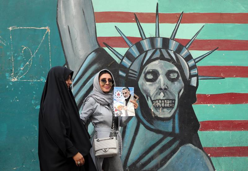 epaselect epa07140552 An Iranian woman (C) holds a poster of Iranian Major General in the Islamic Revolutionary Guard Corps (IRGC) Qasem Soleimani as she walks past a mural depicting a skull-faced Statue of Liberty during an anti-US demonstration marking the 39th anniversary of US Embassy takeover, near the former US embassy in Tehran, Iran, 04 November 2018. Media reported that thousands of protesters chanting 'Death to America' gathered at the former US embassy in Tehran to mark the 39th anniversary of the start of the Iran hostage crisis. Iranian students occupied the embassy on 04 November 1979 after the USA granted permission to the late Iranian Shah to be hospitalized in the States. Over 50 US diplomats and guards were held hostage by students for 444 days. US President Donald J. Trump's administration announced on 02 November 2018, that it will reimpose sanctions against Iran that had been waived under the 2015 Iran nuclear deal (the Joint Comprehensive Plan of Action, JCPOA). The US sanctions will take effect on 05 November 2018, covering Iran's shipping, financial and energy sectors. In 2015, five nations, including the United States, worked out a deal with the Middle Eastern country that withdrew the sanctions, one of former US President Barack Obama's biggest diplomatic achievements.  EPA/ABEDIN TAHERKENAREH