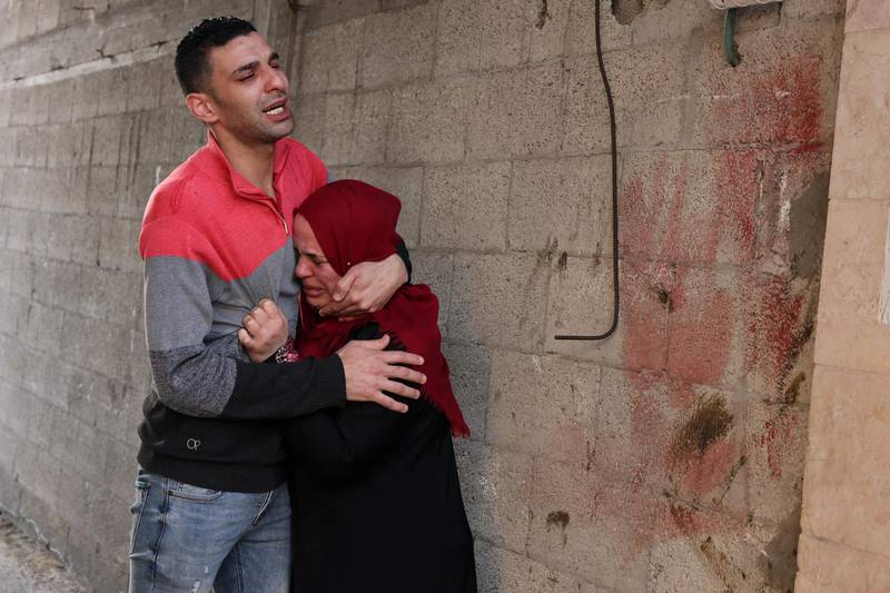 A Palestinian man and woman cry on May 16, 2021 outside their destroyed home in Gaza City, following nearly a week of Israeli air strikes on the Gaza Strip and the Hamas movement firing rocket barrages into Israel.  / AFP / MOHAMMED ABED