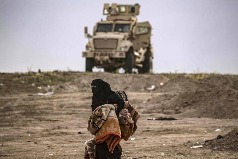 A Syrian woman walks past a military vehicle as hundreds of civilians, who streamed out of the Islamic State group's last Syrian stronghold, headed towards a screening point for new arrivals run by US-backed Syrian Democratic Forces outside Baghouz in the eastern Syrian Deir Ezzor province on March 5, 2019. Shell-shocked and dishevelled, hundreds of women and children stumbled through eastern Syria's windswept desert carrying what little they could after fleeing the IS group's final speck of territory. / AFP / Delil SOULEIMAN