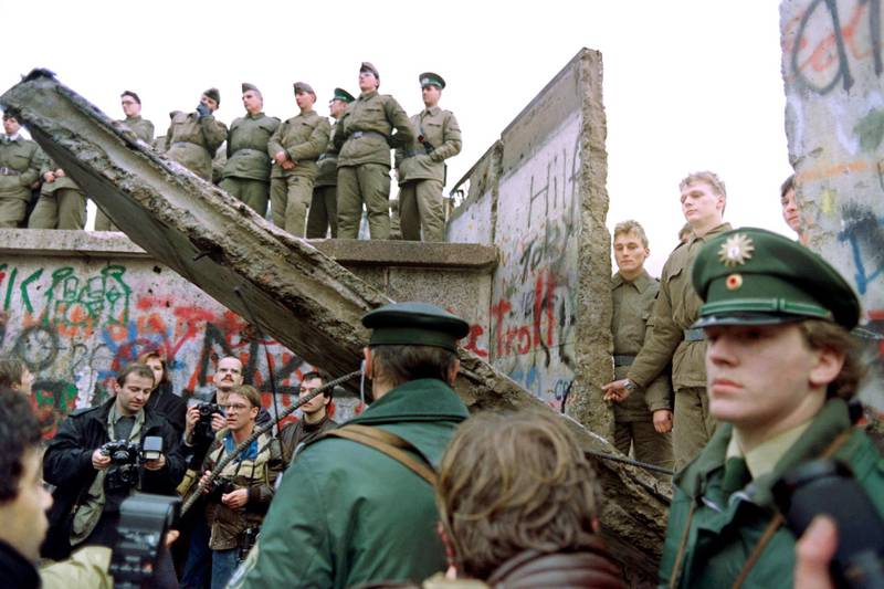 """Two West German policemen prevent people from approaching as East German Vopos stand on and near a fallen portion of the Berlin Wall 11 November 1989. Two days before, Gunter Schabowski, the East Berlin Communist party boss, declared that starting from midnight, East Germans would be free to leave the country, without permission, at any point along the border, including the crossing-points through the Wall in Berlin. The Berlin concrete wall was built by the East German government in August 1961 to seal off East Berlin from the part of the city occupied by the three main Western powers to prevent mass illegal immigration to the West. According to the """"August 13 Association"""" which specialises in the history of the Berlin Wall, at least 938 people - 255 in Berlin alone - died, shot by East German border guards, attempting to flee to West Berlin or West Germany. AFP PHOTO GERERAD MALIE (Photo by GERARD MALIE / AFP)"""