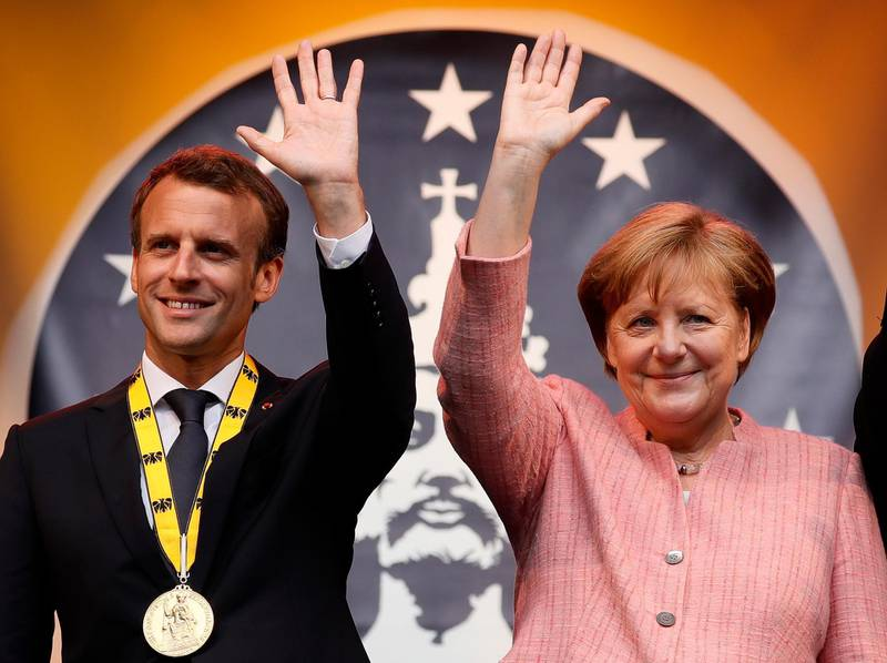 epa06725179 French President Emmanuel Macron (L) and German Chancellor Angela Merkel (R) greet on stage after the Charlemagne Prize (Karlspreis) ceremony at the town hall in Aachen, Germany, 10 May 2018. The International Charlemagne Prize of the German City of Aachen is awarded annually since 1950 to people who have contributed to the ideals upon which Europe has been founded.  EPA/RONALD WITTEK