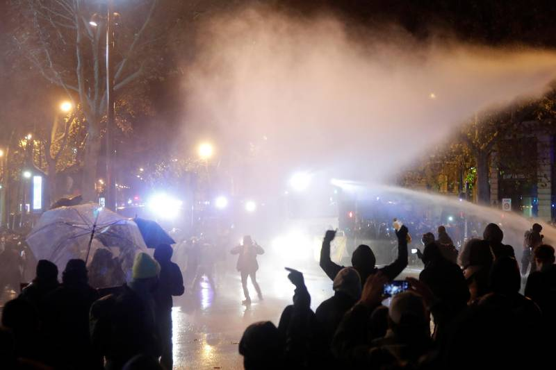 """French police use a water cannon as they face off with demonstrators at the Place de la Republique during a demonstration against the """"Global Security Bill'', that right groups say would make it a crime to circulate an image of a police officer's face and would infringe journalists' freedom in the country, in Paris, France, December 12, 2020.  REUTERS/Charles Platiau"""