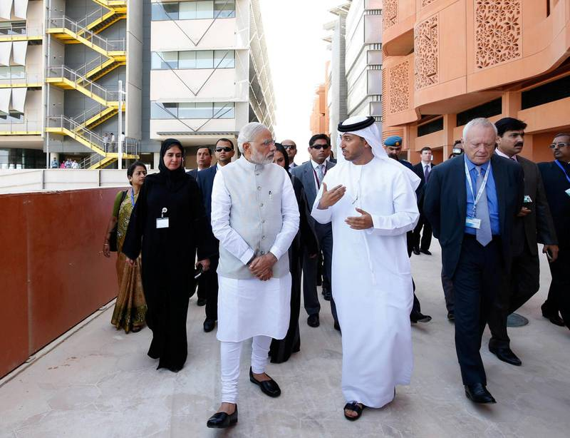 """A picture made available by the United Arab Emirates' official news agency WAM on August 17, 2015 shows Indian Prime Minister Narendra Modi (C-L) talking to an Emirati official during a tour in Masdar City on the outskirts of the rich Emirate of Abu Dhabi. Modi is on a two-day visit, the first by an Indian premier in more than three decades, during which he discussed """"cooperation"""" with oil-rich UAE. AFP PHOTO / RYAN CARTER / WAM / HO  == RESTRICTED TO EDITORIAL USE - MANDATORY CREDIT """"AFP PHOTO / HO / WAM"""" == NO MARKETING NO ADVERTISING CAMPAIGNS - DISTRIBUTED AS A SERVICE TO CLIENTS === / AFP PHOTO / WAM / HO"""