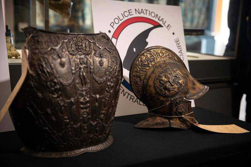 """This picture taken on March 3, 2021, shows a breastplate and a ceremonial helmet during their official restitutions by the French Central Directorate of the Judicial Police (DCPJ) to the Louvre Museum, in Paris. A breastplate and a ceremonial helmet, two """"exceptional"""" objects from the Italian Renaissance, were handed over by the police to the Louvre museum after being found in Bordeaux during an auction linked to an estate. These objects, which belonged to the collection of the Baroness de Rothschild, had been donated to the Louvre in 1922 and stolen in 1983. Estimations say they worth around 500,000 euros. / AFP / Thomas SAMSON"""