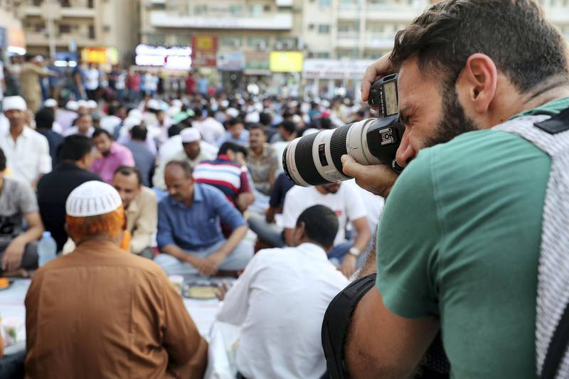 DUBAI , UNITED ARAB EMIRATES , MAY 23 – 2018 :- One of the participant taking photos during the iftar at the mosque near Al Ghubaiba bus station during the Unseen Trails Iftar Walk presented by Gulf Photo Plus and Frying Pan Adventures in Bur Dubai area in Dubai.  ( Pawan Singh / The National )  For Weekender