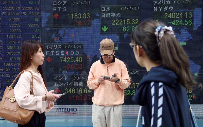 People walk by an electronic stock board of a securities firm in Tokyo, Wednesday, April 25, 2018. Asian shares dipped Wednesday, mirroring a sell-off on Wall Street on worries over slowing growth and falling profits. (AP Photo/Koji Sasahara)