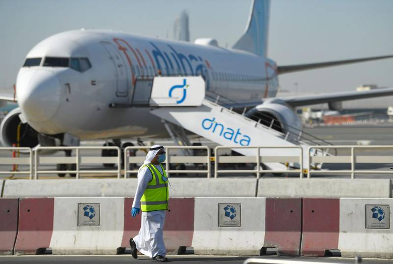 A mask-clad employee walks across a Flydubai aircraft on the tarmac of Dubai International Airport, on April 6, 2020.  / AFP / KARIM SAHIB