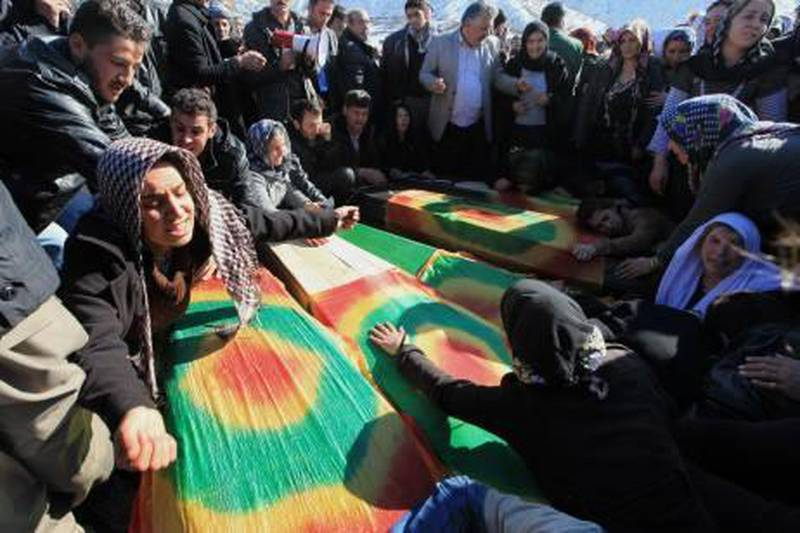 Family members cry over  the coffins of victims as thousands of mourners gathered in Gulyazi village at the border with Iraq, southeast Turkey, Friday, Dec. 30, 2011 for the funerals of 35 Kurdish civilians who were killed in a botched raid by Turkish military jets that mistook the group for Kurdish rebels based in Iraq. Turkish television footage showed people, many weeping and lamenting the dead, as they gathered after the air strikes Wednesday that killed a group of smugglers along the border, one of the deadliest episodes in the conflict between the Turkish state and Kurdish rebels who took up arms in 1984.(AP Photo)