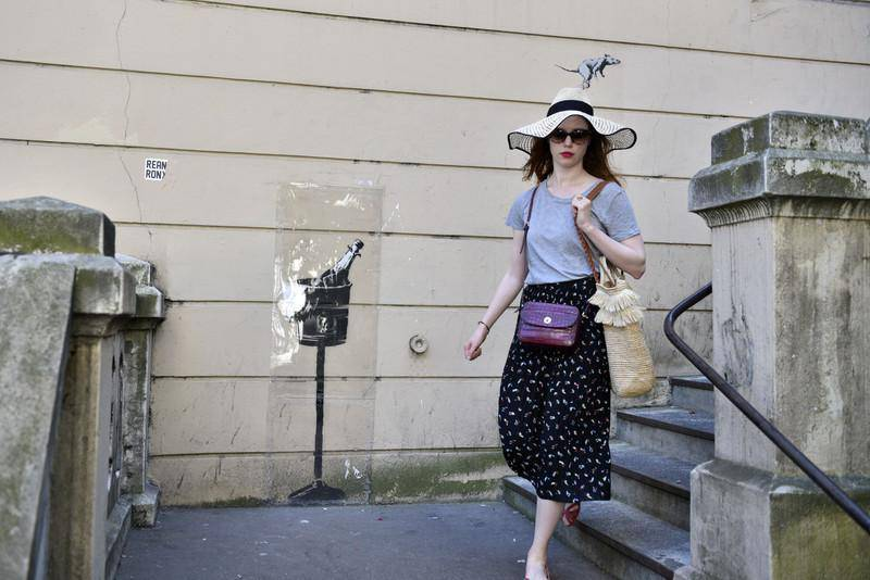 epa06841390 A woman walks by a recent artwork believed to be attributed to Banksy showing a rat on a popped cork from a champagne bottle in the 18th district of Paris, France, 26 June 2018. Several artworks attributed to the anonymous British street artist appeared in the French capital over the last few days.  EPA-EFE/JULIEN DE ROSA