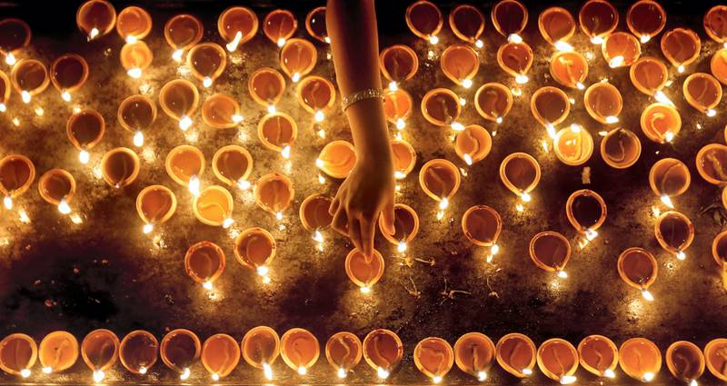 A devotee lights oil lamps at a religious ceremony during the Diwali or Deepavali festival at a Hindu temple in Colombo, Sri Lanka October 18, 2017. REUTERS/Dinuka Liyanawatte     TPX IMAGES OF THE DAY - RC1718C64370