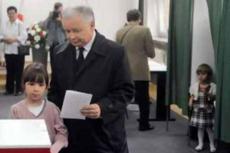 Presidential candidate Jaroslaw Kaczynski, twin brother of the late President Lech Kaczynski killed in a plane crash, prepares to cast his ballot, accompanied by his brother's grand daughters Eva, left, and Martyna, right, in the presidential election in Warsaw, Poland, Sunday, June 20, 2010. Poles are voting Sunday to choose Lech Kaczynski's successor. (AP Photo/Alik Keplicz) *** Local Caption ***  PJO108_Poland_Presidential_Election.jpg