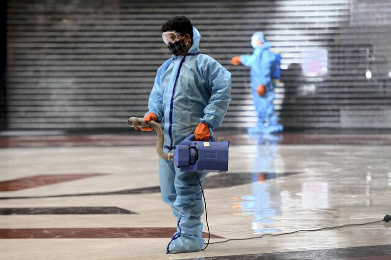 Workers wearing protective gears as a preventive measure against the Covid-19 coronavirus, sanitize the interiors of the Select Citywalk mall in New Delhi on June 6, 2021, after authorities announced the easing of the lockdown in the Indian capital. (Photo by Money SHARMA / AFP)