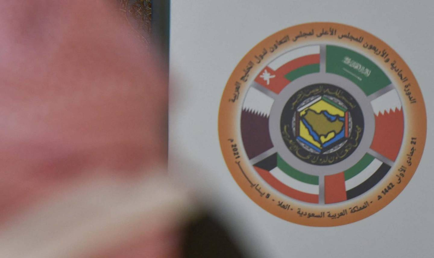 A Saudi journalist is pictured in front of the logo of the Gulf Cooperation Council (GCC) and the Qatari national flag at the media centre ahead of the 41st summit in the city of al-Ula in northwestern Saudi Arabia on January 5, 2021. - Saudi Arabia will reopen its borders and airspace to Qatar, US and Kuwaiti officials said, a major step towards ending a diplomatic rift that has seen Riyadh lead an alliance isolating Doha. The bombshell announcement came on the eve of GCC annual summit in the northwestern Saudi Arabian city of Al-Ula, where the dispute was already set to top the agenda. (Photo by FAYEZ NURELDINE / AFP)