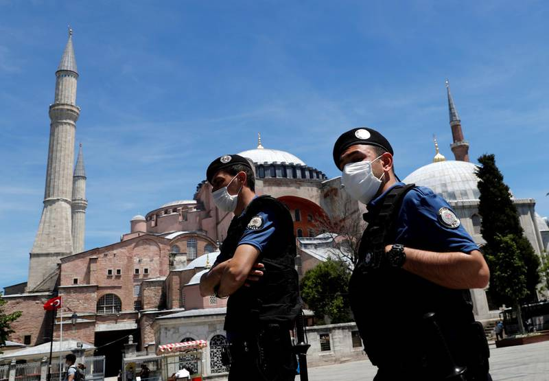 FILE PHOTO: Turkish police officers wearing face masks, with the Byzantine-era monument of Hagia Sophia, now a museum, in the background, patrol at touristic Sultanahmet Square following the coronavirus disease (COVID-19) outbreak, in Istanbul, Turkey, June 5, 2020. REUTERS/Murad Sezer/File Photo
