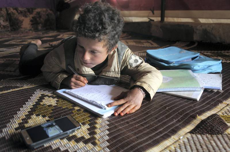 A young pupil follows a lesson on a mobile telephone inside a tent, in a camp for displaced Syrians in the village of Kafr Yahmoul in the northwestern Idlib province, amid the coronavirus pandemic on April 3, 2020. - Like in much of the world, educators in Syria are taking classes online after the country's various regions sent pupils home hoping to stem the COVID-19 pandemic.  But distance learning is no small feat in a country battered by nine years of war, where fighting has displaced millions and the electricity supply is sporadic at best. (Photo by Aref TAMMAWI / AFP)