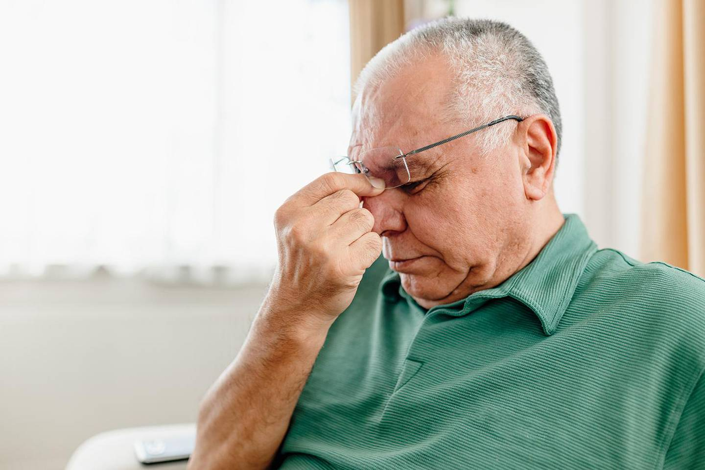 A Distraught Senior Man Suffering From a Migraine