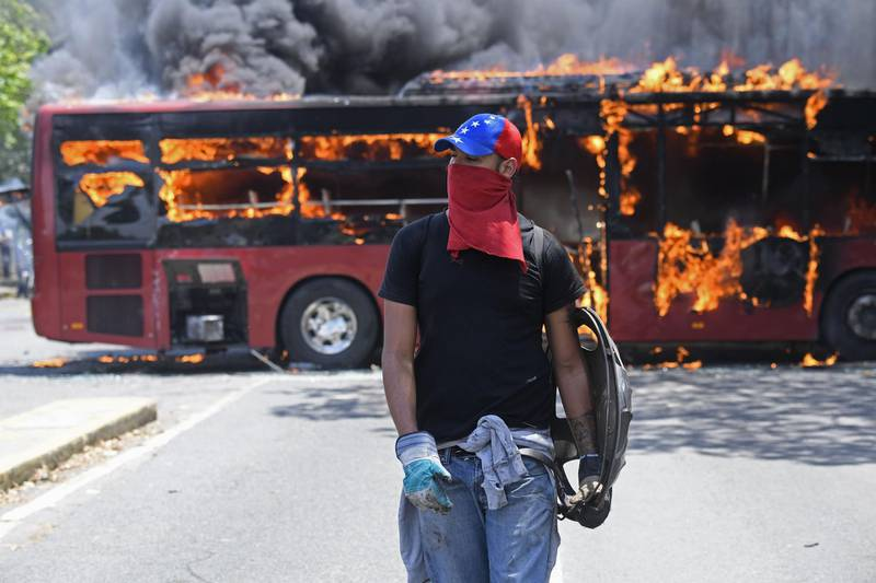 """TOPSHOT - An opposition demonstrator walks near a bus in flames during clashes with soldiers loyal to Venezuelan President Nicolas Maduro after troops joined opposition leader Juan Guaido in his campaign to oust Maduro's government, in the surroundings of La Carlota military base in Caracas on April 30, 2019. Guaido -- accused by the government of attempting a coup Tuesday -- said there was """"no turning back"""" in his attempt to oust President Nicolas Maduro from power. / AFP / Federico PARRA"""