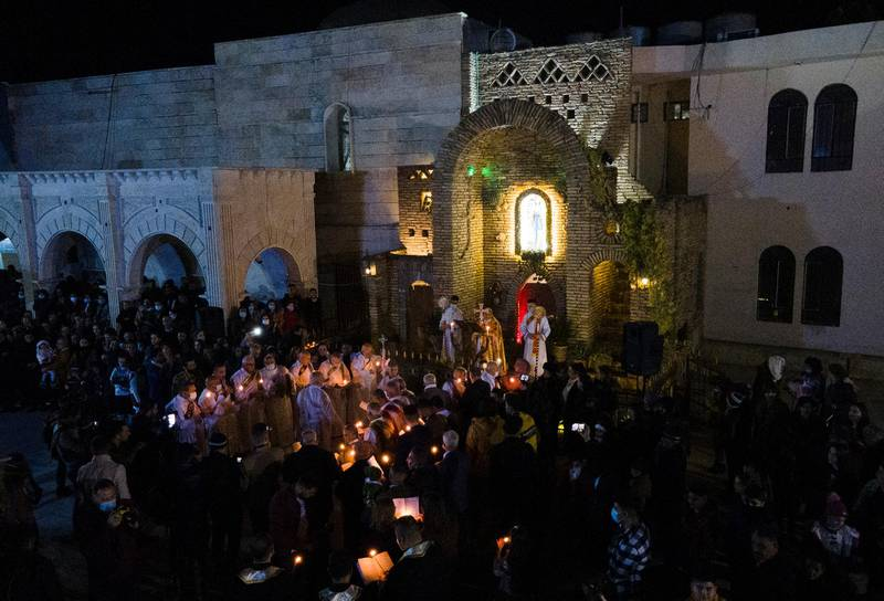 An aerial picture shows Iraqi priests leading the Christmas eve mass at the Syriac Catholic Church of the Immaculate Conception (Al Tahira-l-Kubra), in the predominantly Christian town of Qaraqosh, in Nineveh province, some 30 kilometres from Mosul, on December 24, 2020. (Photo by Zaid AL-OBEIDI / AFP)